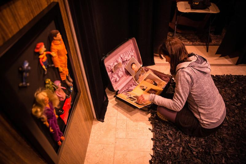 "A visitor examines personal artifacts in the interactive exhibit ""Memory in a Void,"" filled with Joe Dulude II's childhood memories. Photo credit of Matthew Cavanaugh"