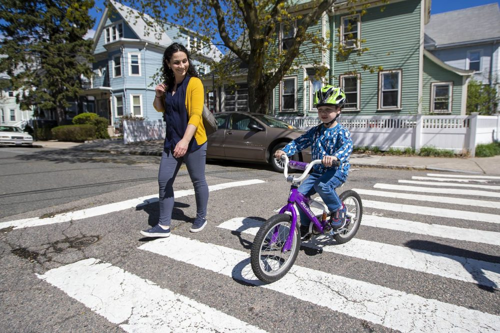 Elizabeth Pinsky walks along side of her son Ben while he rides his bicycle home along Elm St. in Somerville. Photo by Jesse Costa for WBUR