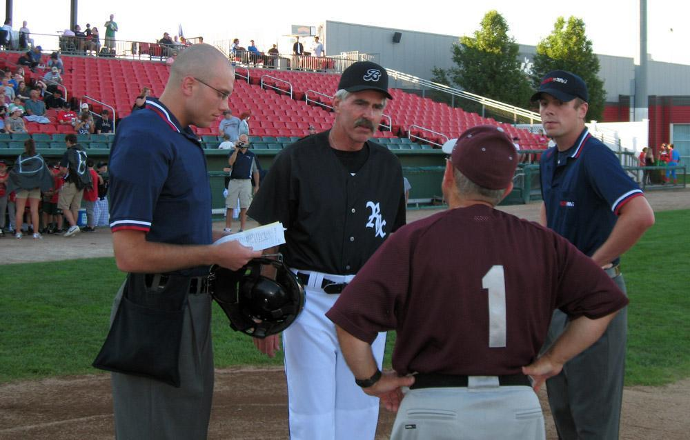 Bill Buckner, in black, speaks with umpires and the opposing manager before a 2011 Brockton Rox game. Photo by Anthony Brooks for WBUR