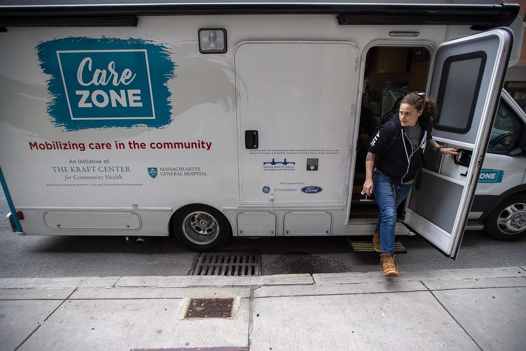 Sarah Mackin exits the Care Zone van after it parks on Haverhill St. near by North Station. They will mobilize and walk around the area to look for opioid users who need assistance. Photo by Jesse Costa for WBUR