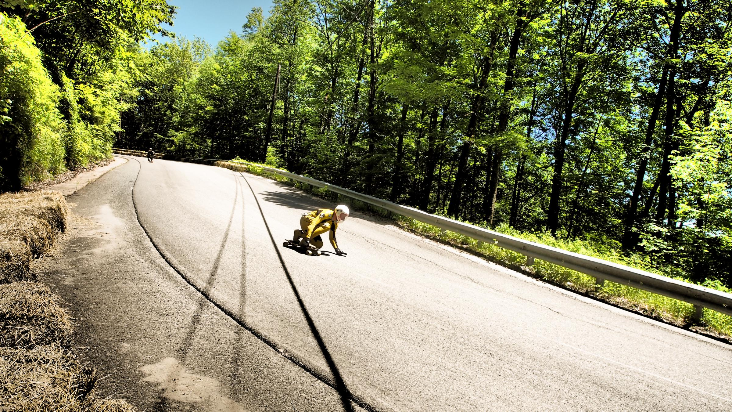 "A racer on Whitcomb Hill Road crouches low approaching a part of the racetrack known as ""the left slide."" Photo by Ben James for NEPR"