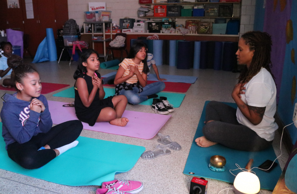 As part of the Come and Learn Mindfulness program at Curiale School in Bridgeport, yoga instructor Shinda DeRosa sits cross-legged with her students, encouraging them to place their hands over their hearts and meditate about their loved ones. Photo by Christian Carter for WSHU.