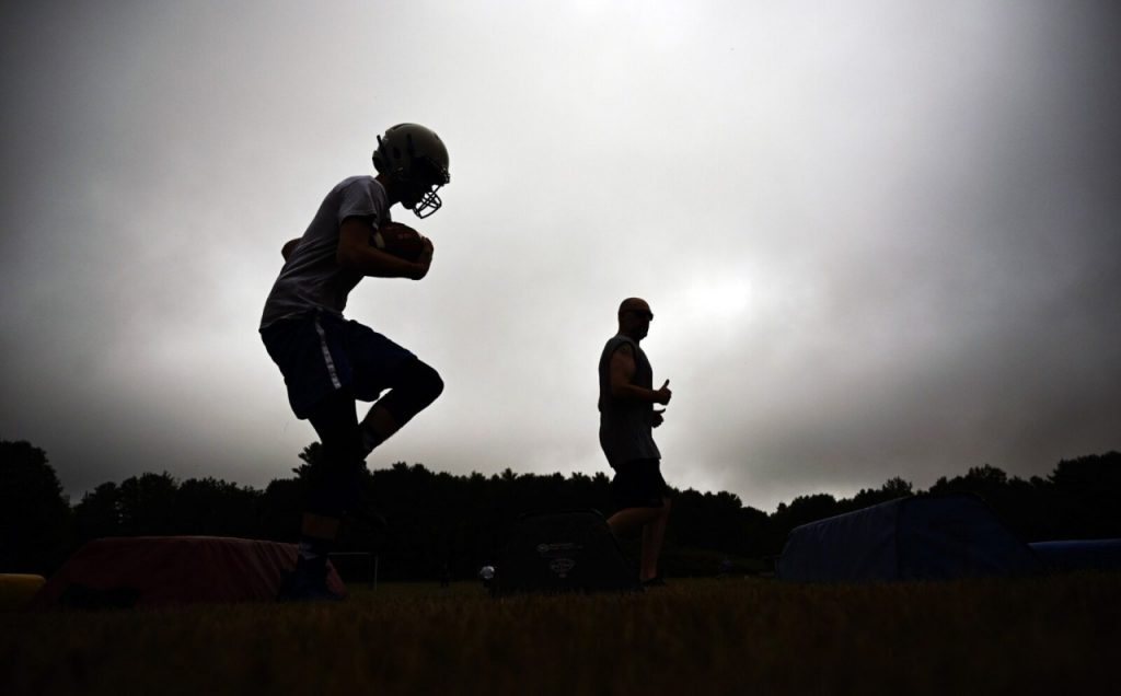 Assistant coach Jon Gallant, in the background, watches as players run drills at Old Orchard Beach's first football practice of the season Monday morning. Shawn Patrick Ouellette_Staff Photographer
