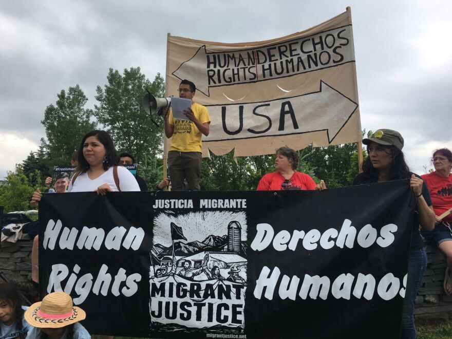 """People hold up signs that say """"Human Dignity/ Derechos Humanos"""" in support of migrant farmworkers in Vermont."""