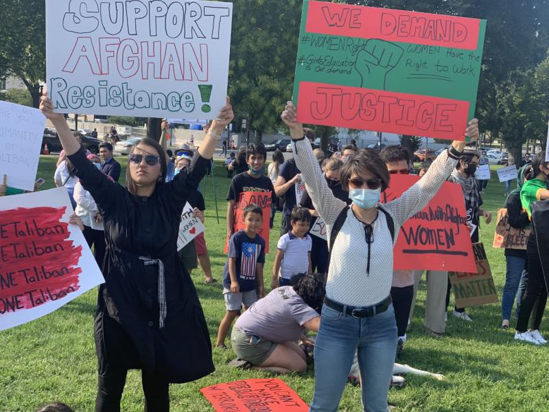 Two protesters hold protest signs