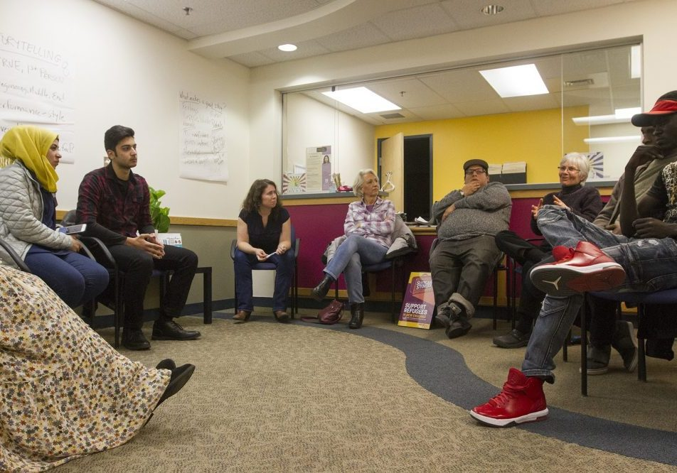 "The organizer behind the International Institute of New England and Massmouth's live storytelling collaboration ""Suitcase Stories"" sees it as a way to break down cultural barriers and turn strangers into neighbors. Here, a group of potential storytellers gather at the International Institute's Lowell office for a storytelling workshop. Photo by Joe Difazio for WBUR"