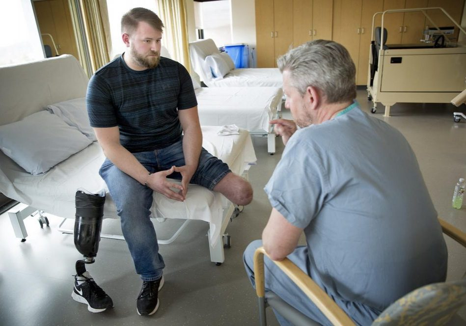 Brandon Korona, an Army veteran whose left leg was injured in an IED explosion in Afghanistan, talks with Dr. Matthew Carty at Brigham and Women's Faulkner Hospital in Boston. Photo by Robin Lubbock for WBUR