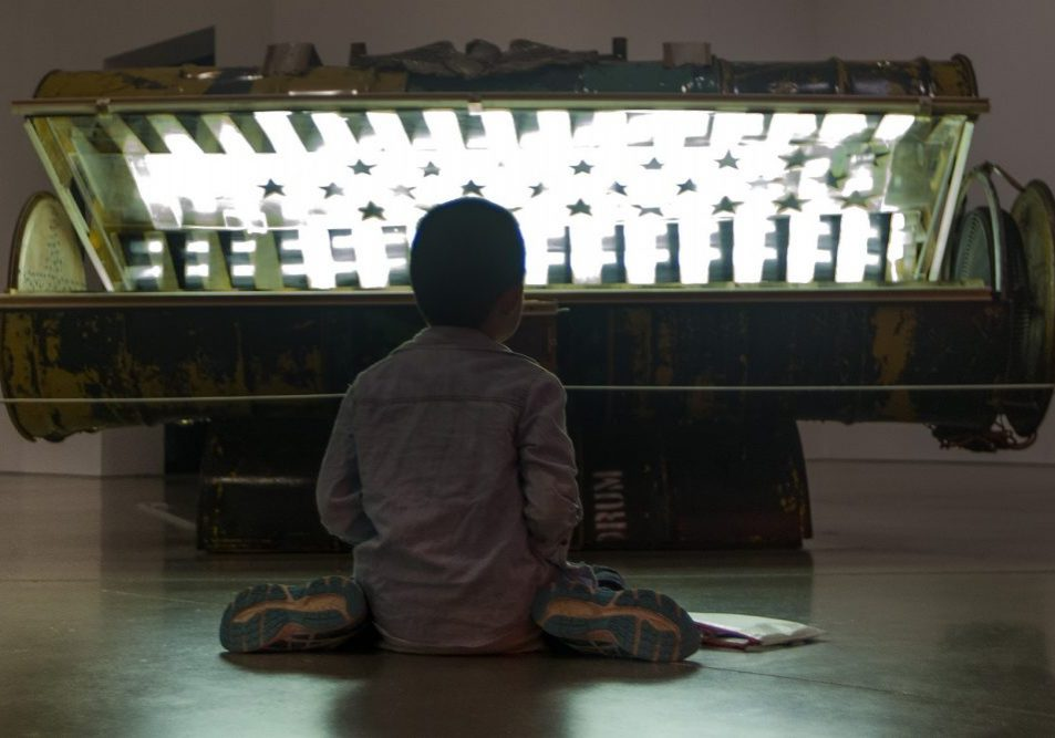 "Nine-year-old Danny Zheng colors on the floor in front of Nari Ward's ""Tanning Bed."" Photo by Jesse Costa for WBUR."