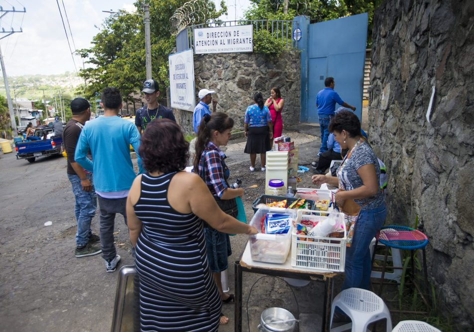 Shortly after being teleased, deportees purchase snacks and other various items from a woman set up outside of the Centro de Atención integral a Migrante (Comprehensive Migrant Care Center) in San Salvador. Photo by Jesse Costa for WBUR