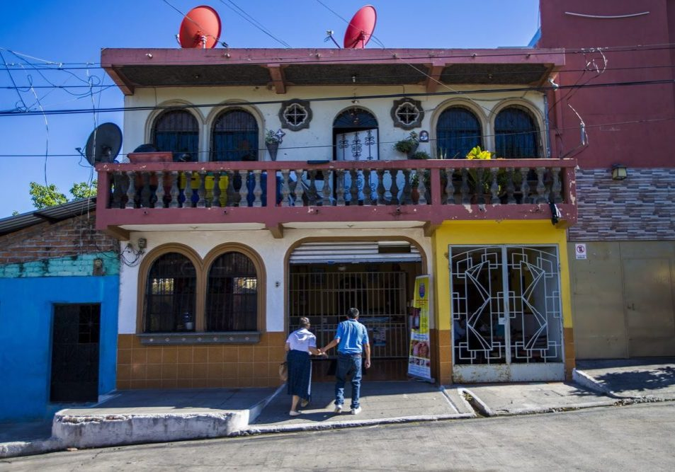 A couple walk hand-in-hand into Panaderia Pacita Quintanilla in San Vicente, El Salvador. Photo by Jesse Costa for WBUR