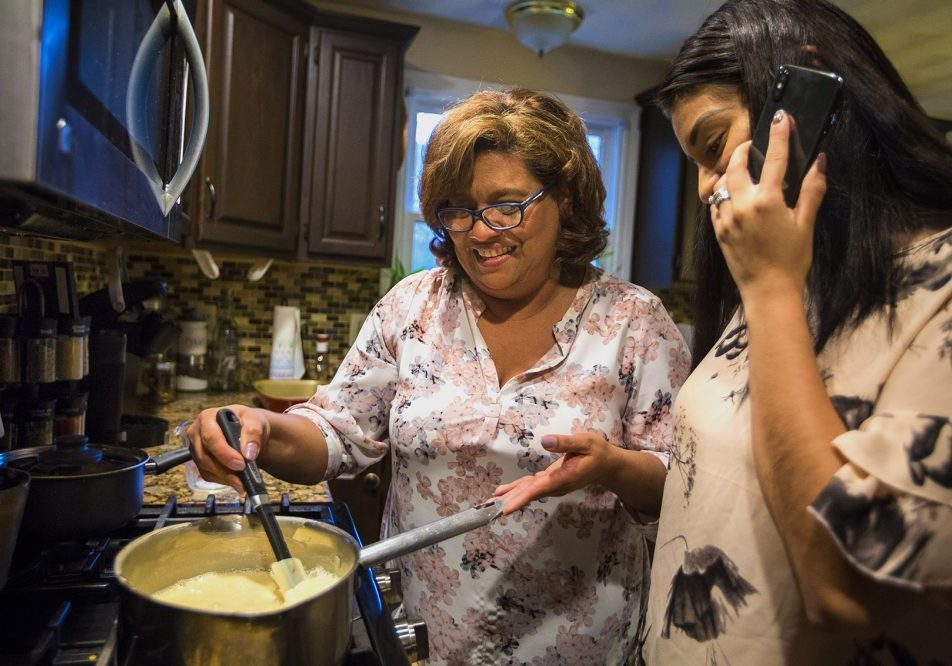 As Irma Flores stirs mik in a pan, her daughter Gabriela Portillo-Perez speaks with her grandmother Isabel on the phone in El Salvador. Photo by Jesse Costa for WBUR.