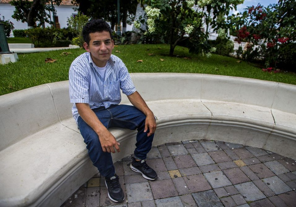 Orlando sits in a plaza in Metapán, El Salvador. Photo by Jesse Costa for WBUR