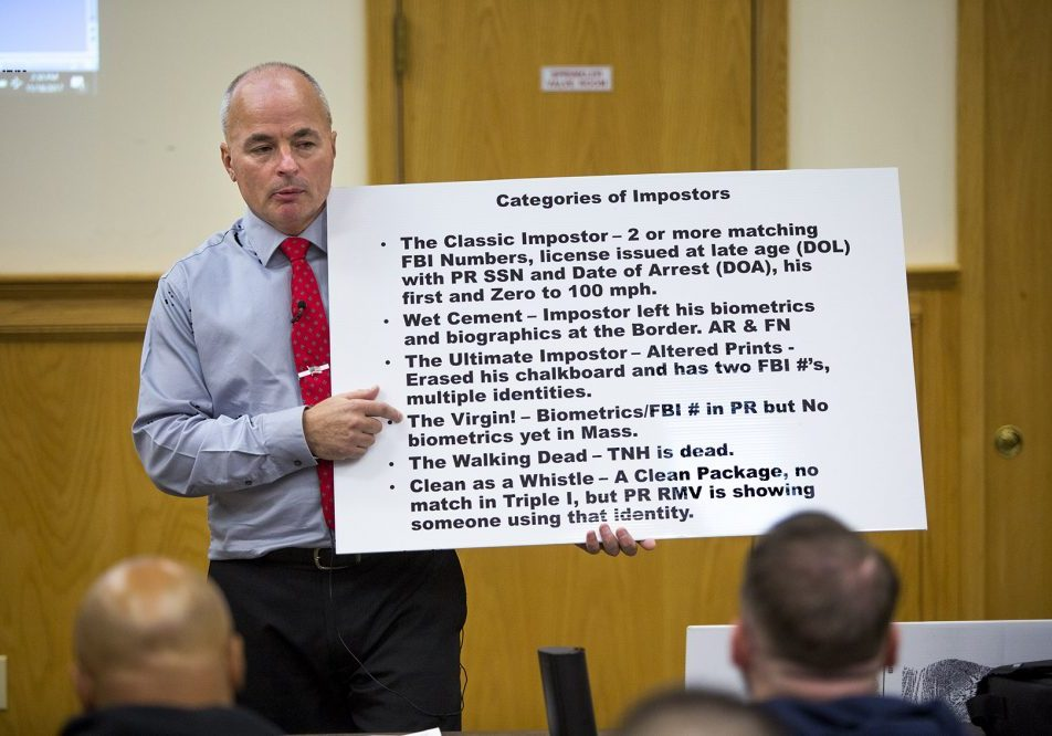 "Officer James Scott of the Saugus Police Department holds up a placard with the categories of so-called ""impostors"" during an impostor training class at Bristol County Jail and House of Correction in North Dartmouth. Photo by Jesse Costa for WBUR"
