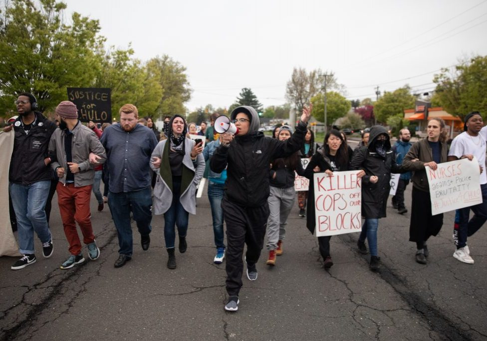 Community organizer Kerry Ellington (center) leads a chant during a march to the Wethersfield mayor's house on May 3, 2019 following the release of videos showing a police officer shooting an 18-year-old after a traffic stop. (Ryan Caron King/Connecticut Public)