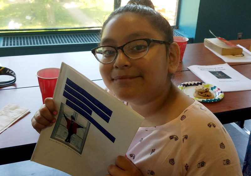Angelina Morales holds her Connecticut history chapter book; Chapter 2 is about the African-American dancer, Dollie McLean. Photo by Tema Silk for NEPR