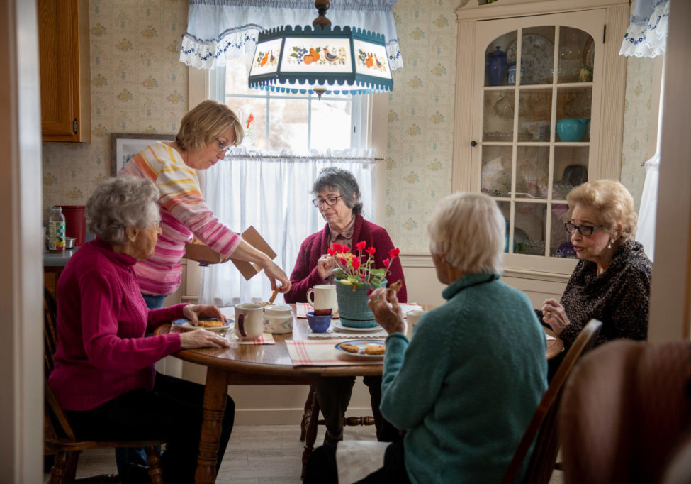 Dorothy Buchanan's daughter, Beth, serves tea, while Dorothy Murray's daughter, Bonnie Parsons (third from left), sits with the three 100-year-old Dots. (Rebecca Conley / Maine Public)