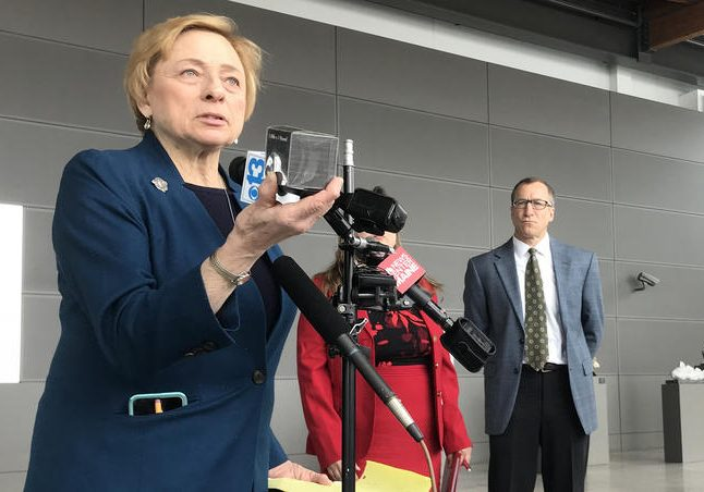 Gov. Janet Mills holds up a pound of carbon at a press conference at the Portland Jetport on Thursday. Photo by Fred Bever for Maine Public