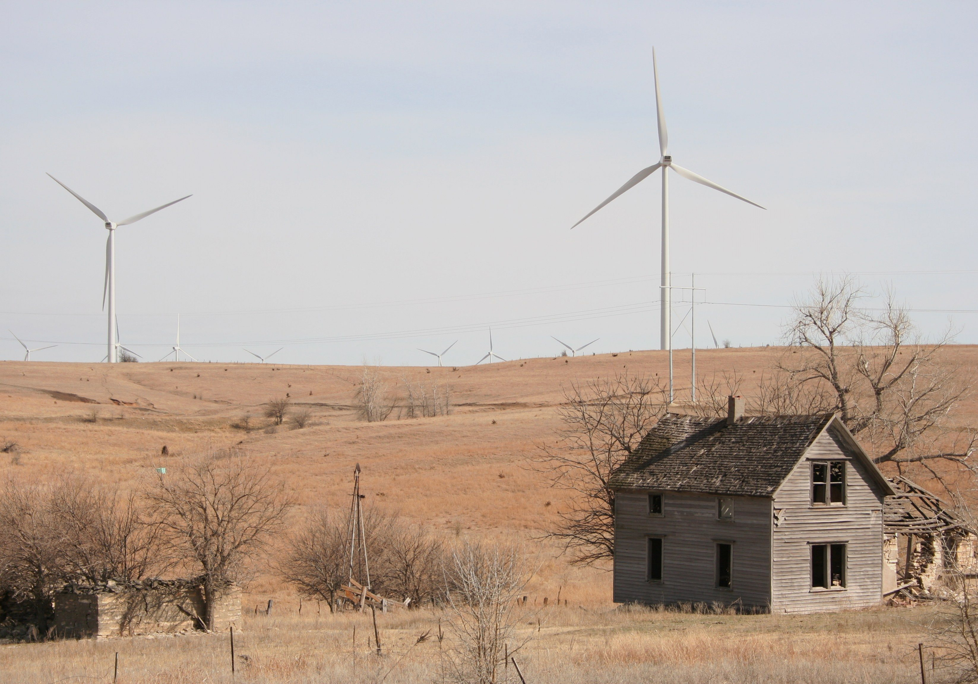 Abandoned farmhouse with turbines in background. Meridian Way Wind Farm, Cloud County, Kansas. Photo by Phil Warburg