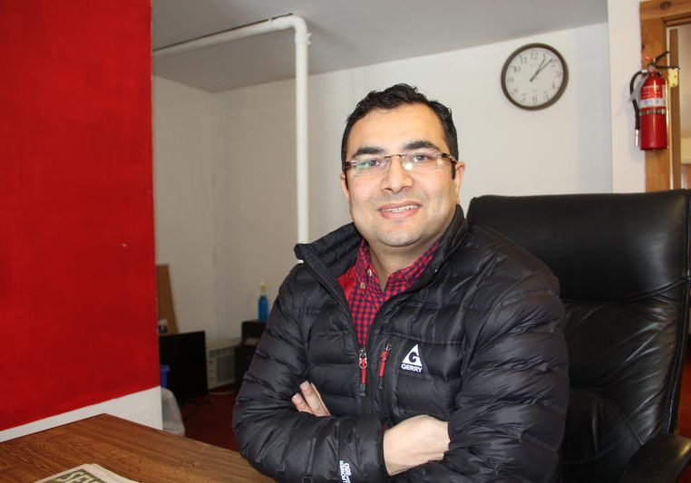 Bhuwan Sharma, co-owner of Burlington Employment Agency, at his Old North End office. He said his business has plateaued due in large part to Bhutanese-Nepali refugees moving from Vermont to Columbus, Ohio. Photo by Bayla Metzger for VPR