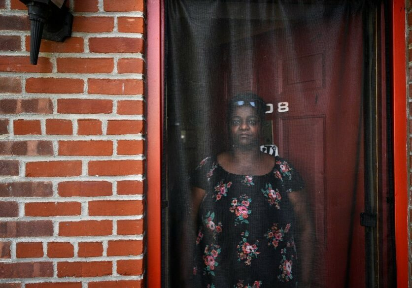 Dione Dwyer in front of her home on Aug. 30, 2021. Dwyer, a single mother, has lived in affordable housing in Bridgeport for 19 years. She is the system change fellow at the P.T. Barnum complex. Prior to finding affordable housing, Dwyer was jumping between staying with relatives while trying to maintain stability in her children's lives. (Allison Minto/Connecticut Public)