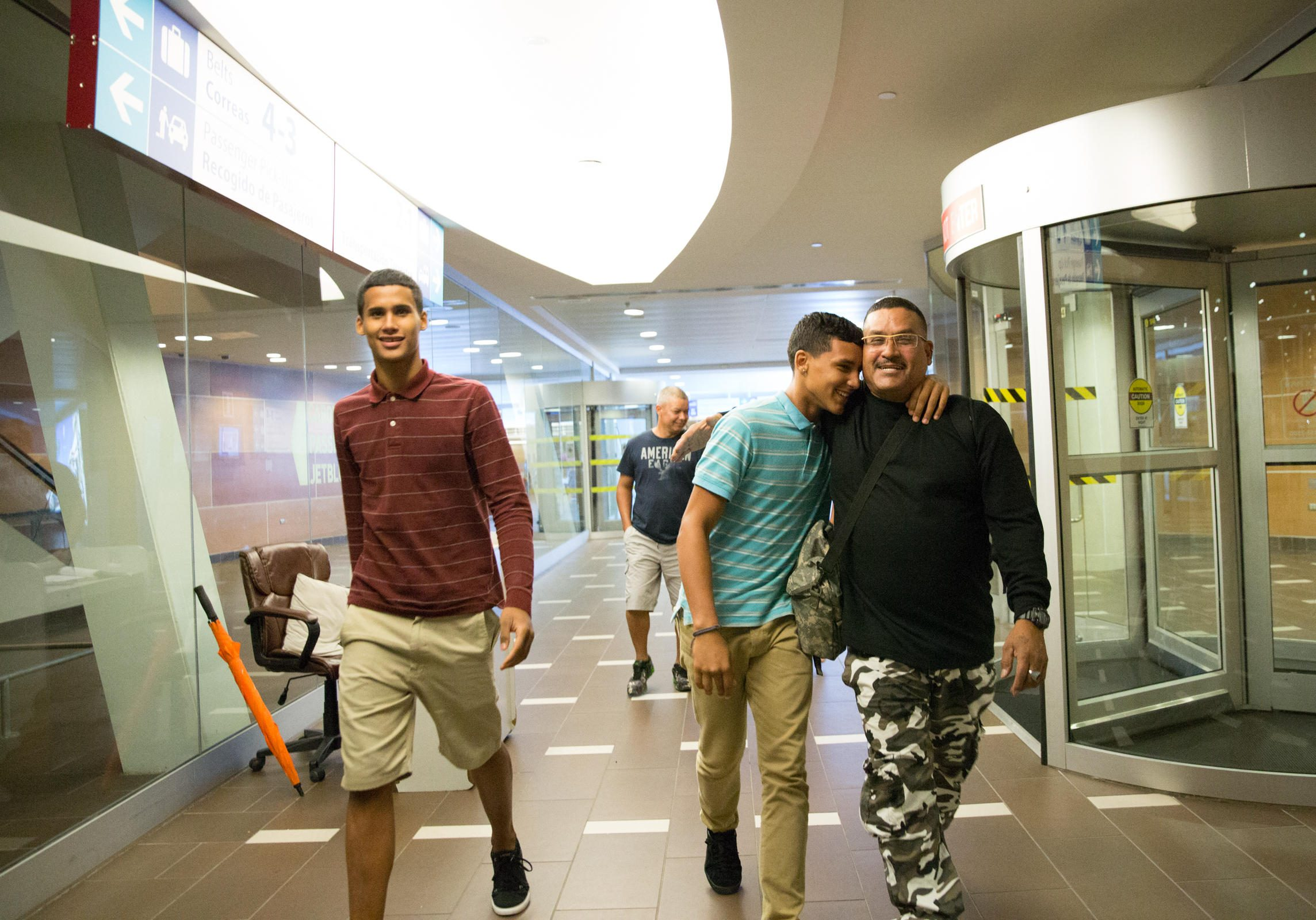 Guillermo Class reunites with his two sons in the San Juan Airport. He sold his car to fly them back to Hartford. Photo by Ryan Caron King for WNPR