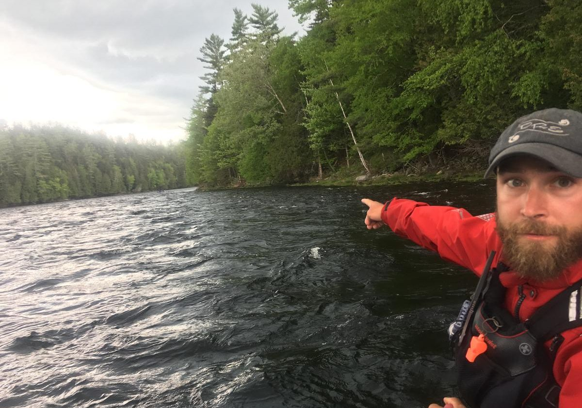 Kevin Ross, a rafting guide for Dead River Expeditions, points to a section of the Kennebec River Gorge where CMP proposes a major transmission line crossing. It would arc over an otherwise undeveloped seven mile stretch of the river. Ross opposes the plan, but CMP and other stakeholders have struck a mitigation deal that would include donations of recreational land and funding for economic development in the West Forks area. Photo by Fred Bever for Maine Public