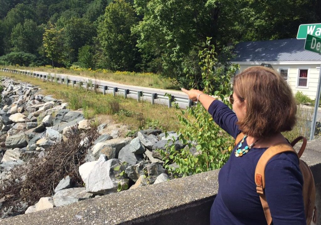 Karin Hardy points to land along Ball Mountain Brook in Jamaica where her house stood before Tropical Storm Irene swept it away. Hardy's former house was not in the FEMA flood zone and she did not have flood insurance. Photo by Howard Weiss-Tisman for VPR