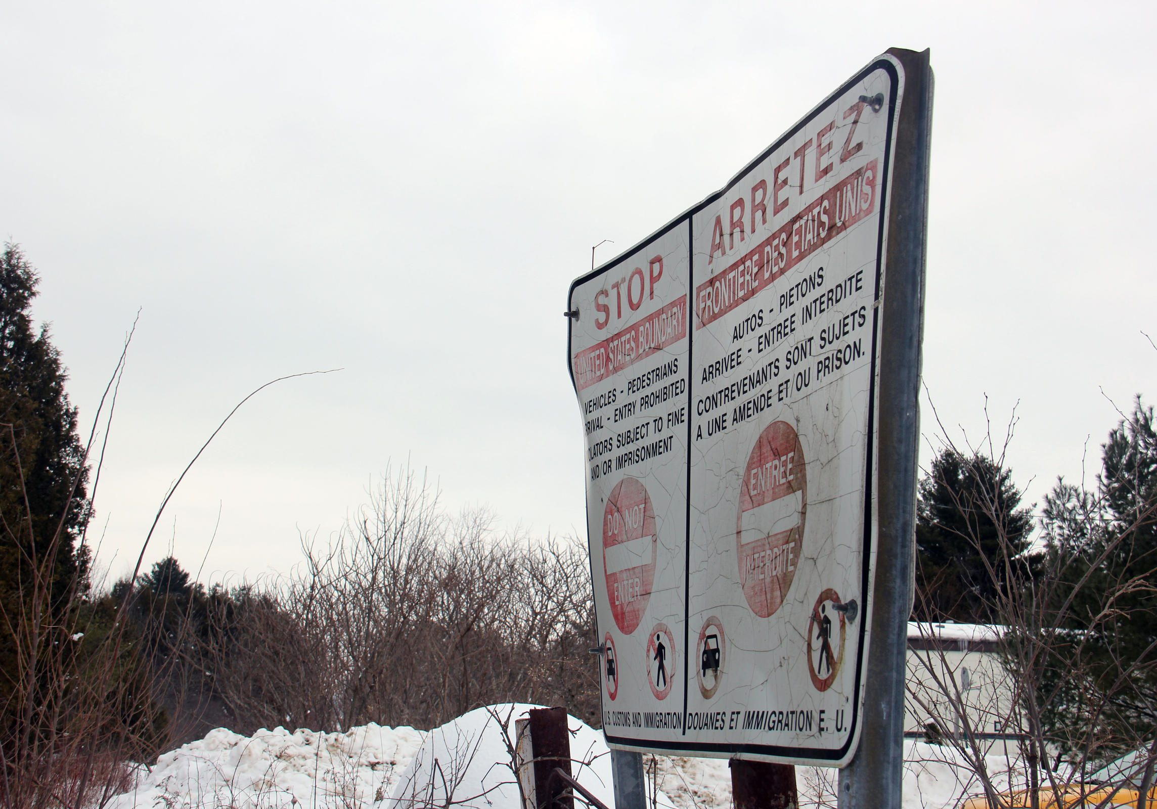 This sign marks the Canadian side of the border at one rural area where many people are crossing illegally into Canada. Mamadou was in the woods somewhere within 20 miles of here. Photo by Kathleen Masterson for NENC