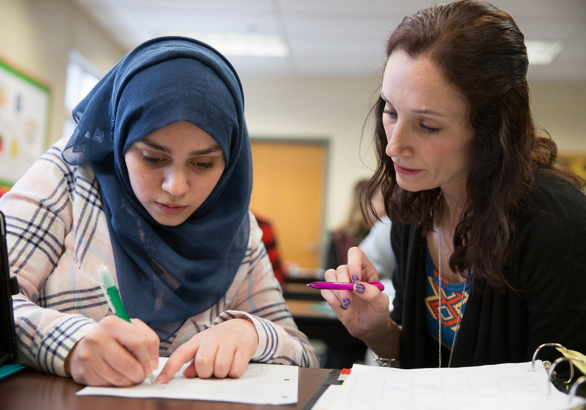 Ghena works on math schoolwork with her guided study teacher Karen Stark . Photo by Ryan Caron King for NENC