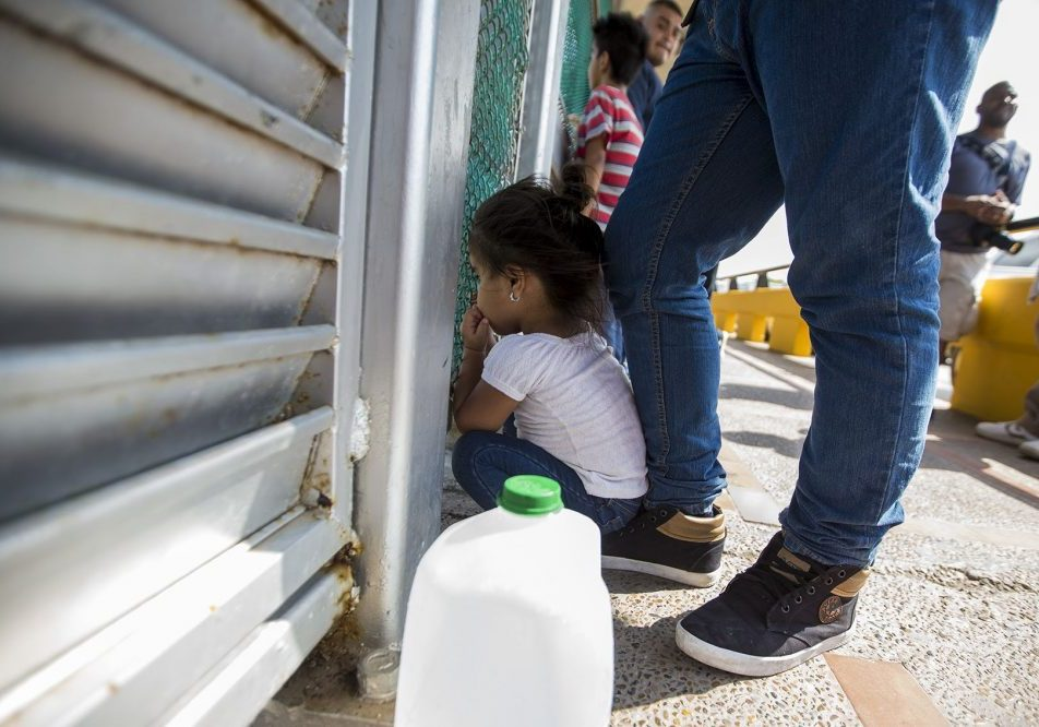 A 3-year-old from Honduras peers through a fence at the U.S.-Mexico border while her family waits to apply for asylum. Photo by Jesse Costa for WBUR