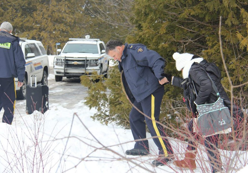 A Canadian police officer offers a hand to a migrant crossing the U.S.-Canada border near Champlain, New York on Wednesday. The Royal Canadian Mounted Police are reporting surges in illegal crossings in Canada in recent months. Photo by Kathleen Masterson for VPR