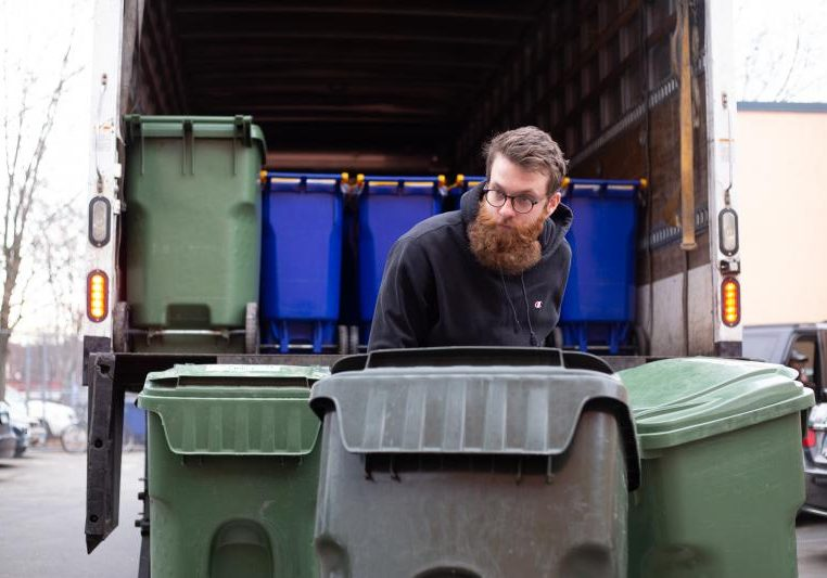 Alex Williams, with Blue Earth Compost, loads barrels of food waste into a truck during a recent food scrap pickup run in Hartford. Photo by Patrick Skahill for Connecticut Public Radio