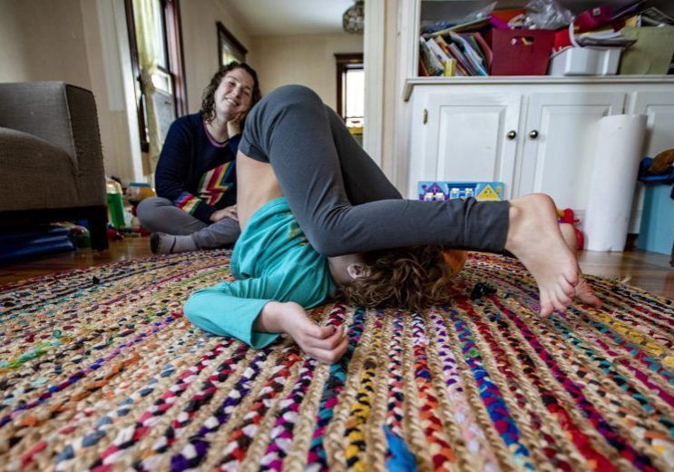 Hallel with their mother in the family's living room. (Jesse Costa/WBUR)
