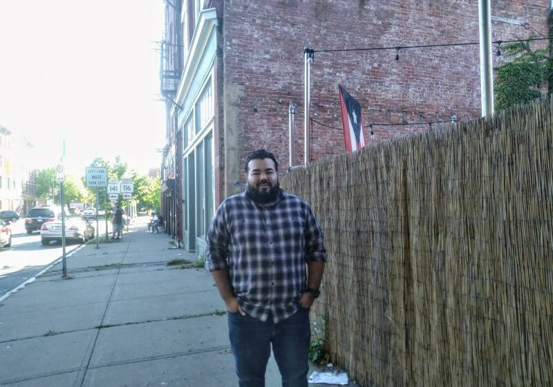 A photo of Jonathan Soto standing on a sidewalk in Holyoke, Mass. Soto survived Hurricane Maria and arrived here from Puerto Rico a few years ago.
