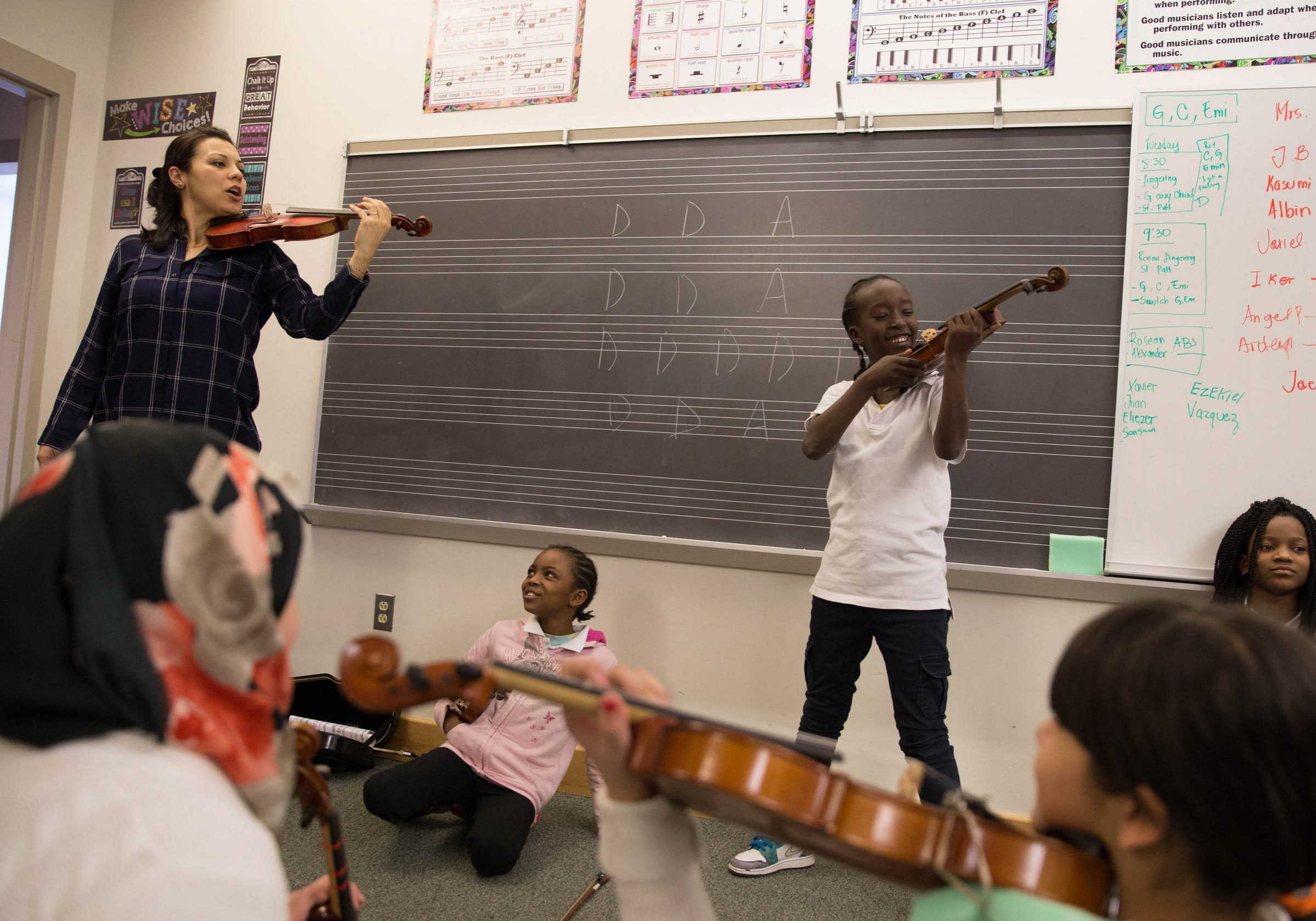 Yaira Matyakubova leads the violin class for young refugees. Photo by Ryan Caron King for WNPR
