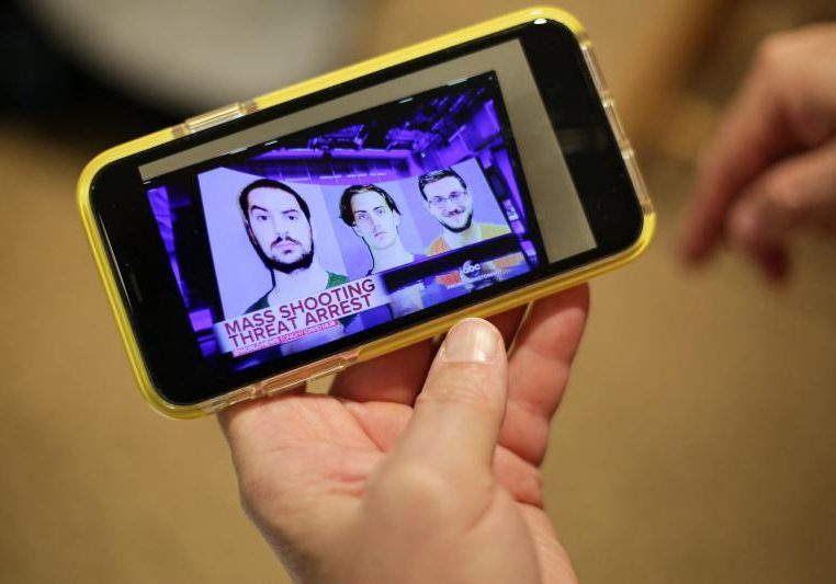 Lee Ann Potter shows a video of Brandon Wagshol (left) on her cell phone. (Ryan Lindsay/Connecticut Public Radio)