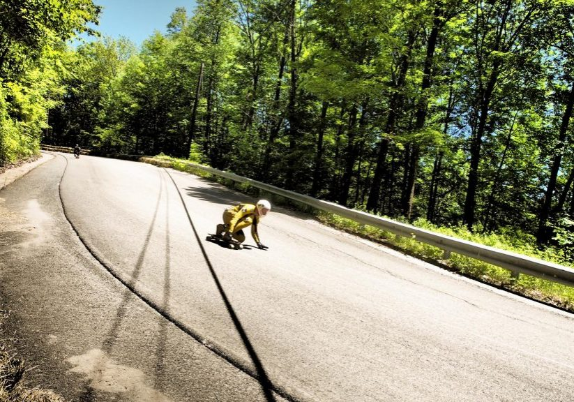 """A racer on Whitcomb Hill Road crouches low approaching a part of the racetrack known as """"the left slide."""" Photo by Ben James for NEPR"""