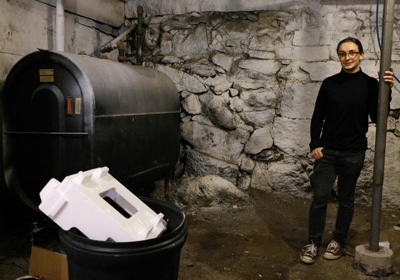 Devin Wilkie in the basement of his oil-heated home in Lebanon. Wilkie doesn't have a lot of money to spend on a more efficient heating system, he said, but he's making affordable improvements to lower his carbon footprint. Photo by Britta Greene for NHPR