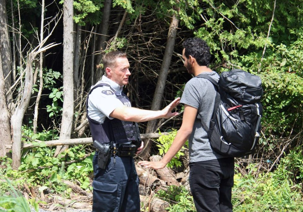 A Canadian police officer warns a young man from Yemen that if he illegally crosses into Canada in between checkpoints he will be arrested. If he proves to not be a threat to the public, the officers will help him fill out the asylum request paperwork. Photo by Kathleen Masterson for VPR